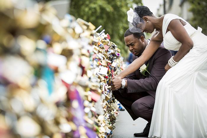 bride and groom placing lock Paris bridge