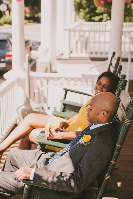 bride and groom in rocking chairs on inn porch