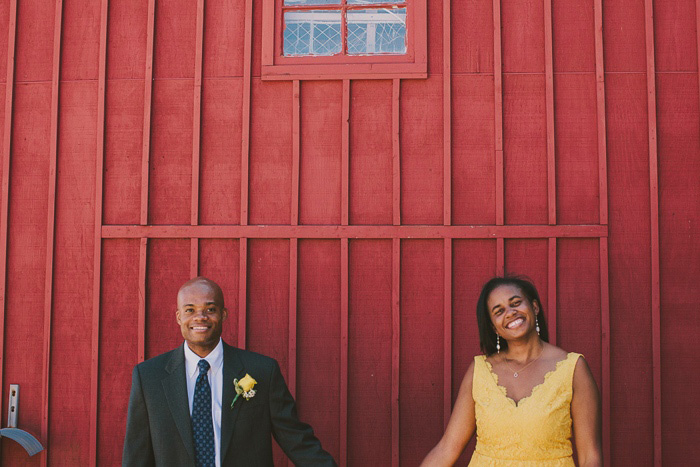 bride and groom in front of red building