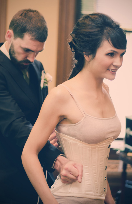 groom tying bride's corset