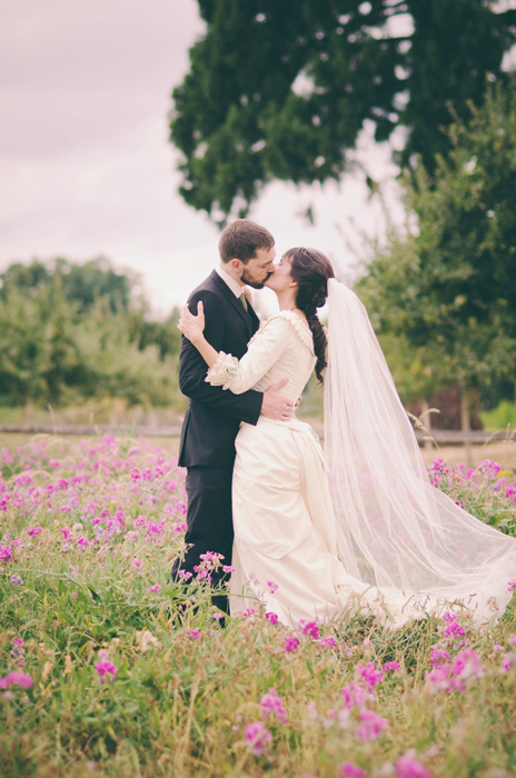 bride and groom kissing in field of flowers