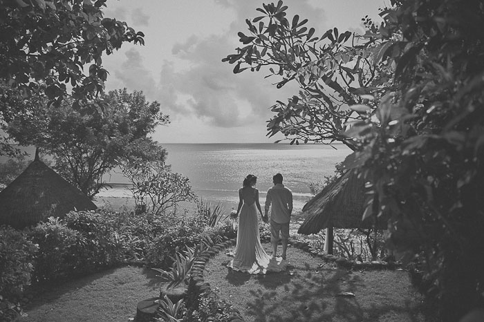 bride and groom standing by the ocean