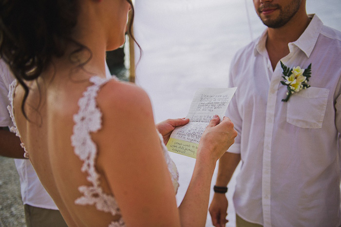 bride reading her vows on the beach