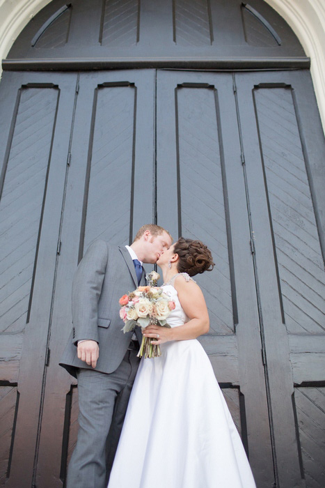 bride and groom kissing in front of church