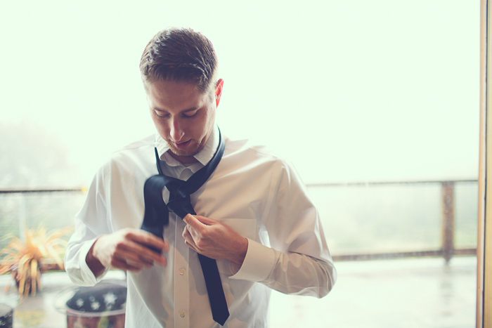 Groom tying hi tie