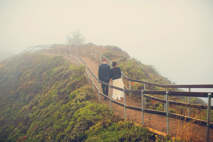 bride and groom walking along wooden path