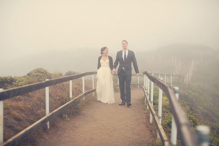 bride and groom walking through the fog