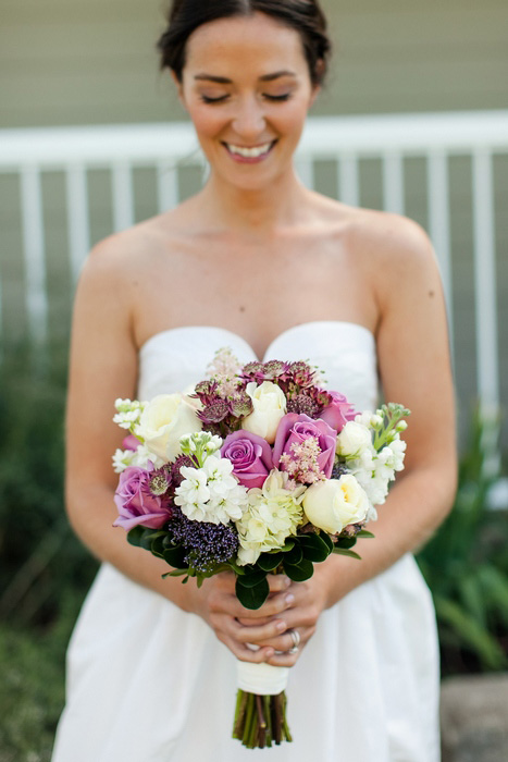 bride with purple and white wedding bouquet