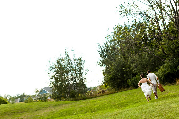bride and groom running with suitcase