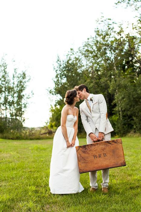 groom holding vintage suitcase