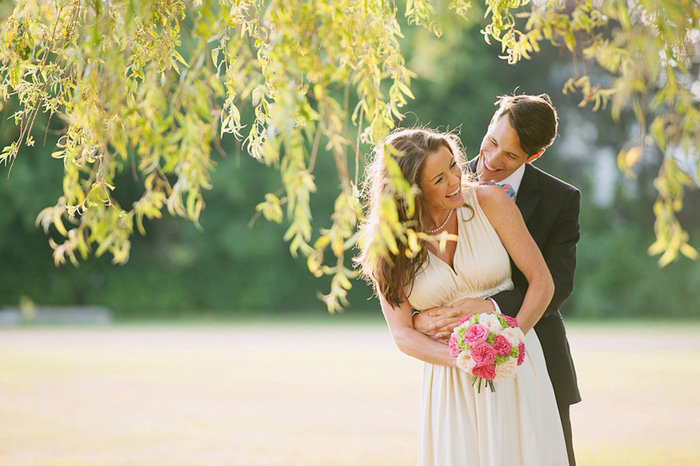 bride and groom beneath a willow tree