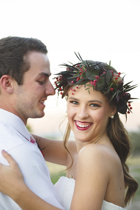 bride wearing red and green flower crown