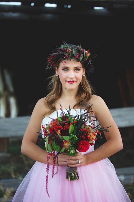 bride with red orange and green wedding bouquet