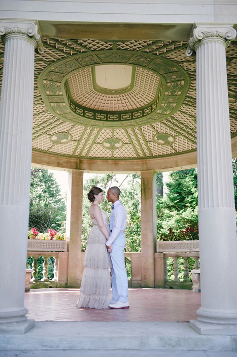bride and groom in park gazebo