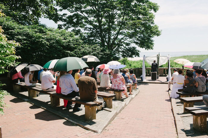 wedding guests with umbrellas at outdoor wedding ceremony