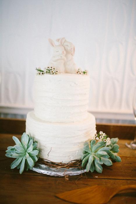 white wedding cake with succulents and rabbit cake topper