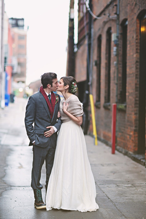 bride and groom kissing in alleyway