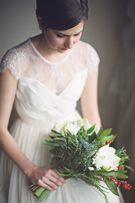 bride in dress with short sleeves and winter bouquet