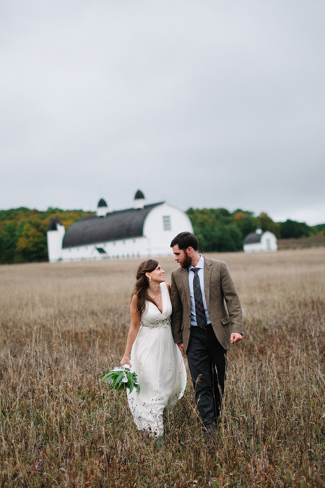 bride and groom walking though farm fields