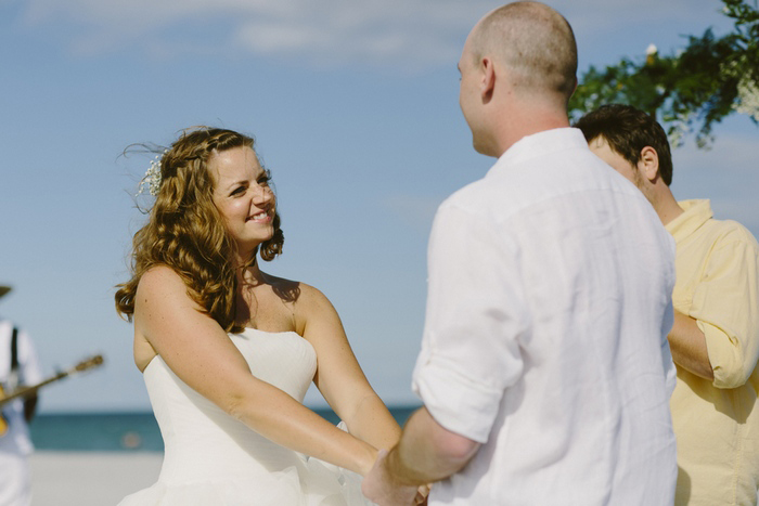 bride and groom exchanging vows on the beach