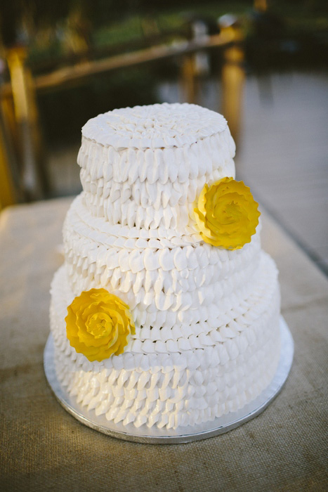 white ruffle wedding cake with yellow flowers