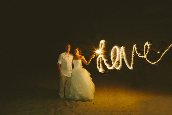 bride and groom with sparklers on the beach