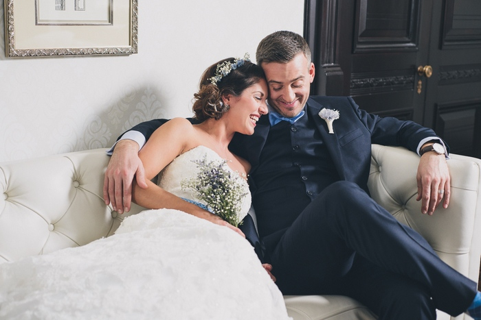 bride and groom cuddling on the couch