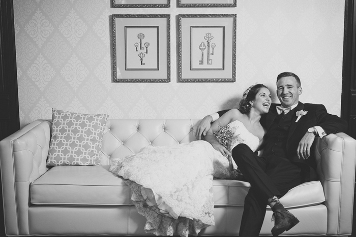 bride and groom laughing on the couch