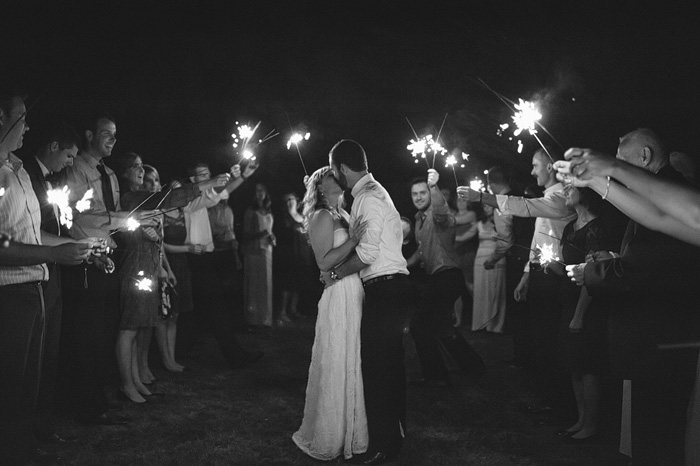 bride and groom kissing under sparkler send-off