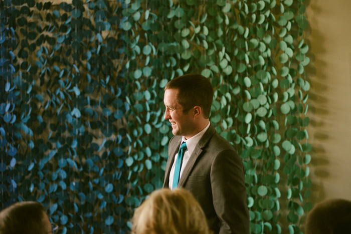 groom in front of ombre ceremony backdrop