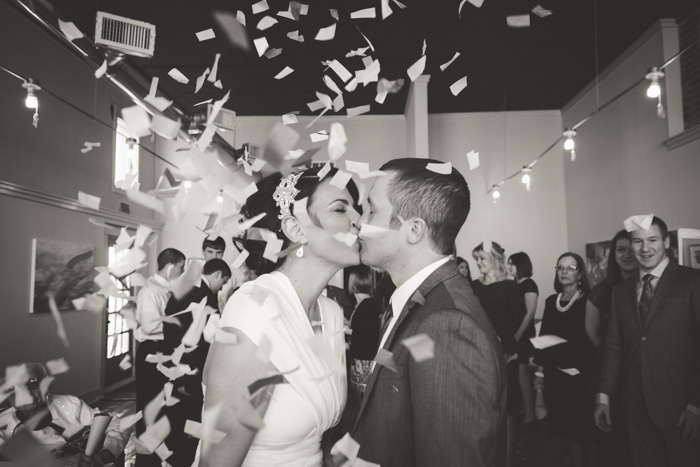 bride and groom kissing during confetti toss