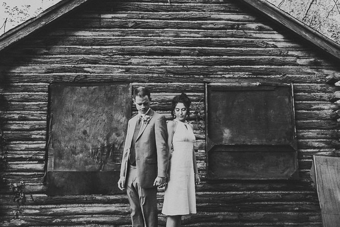 bride and groom in front of abandoned log cabin