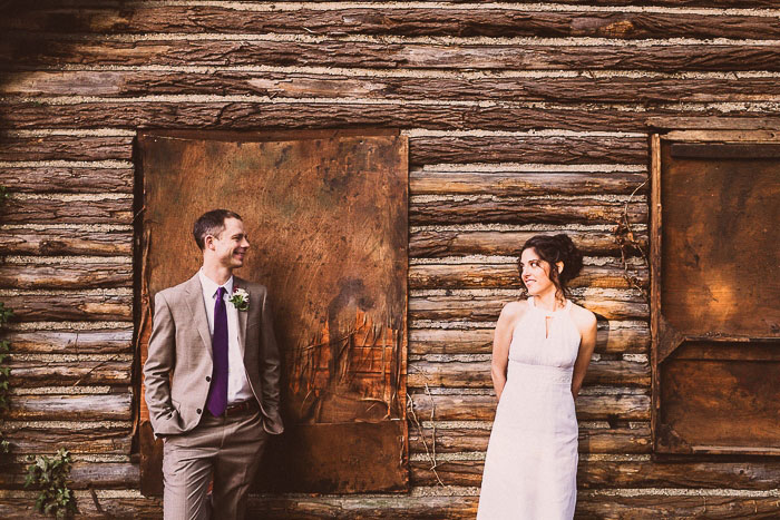 wedding portrait in front of log cabin