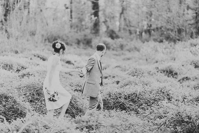 bride and groom walking through overgrown field
