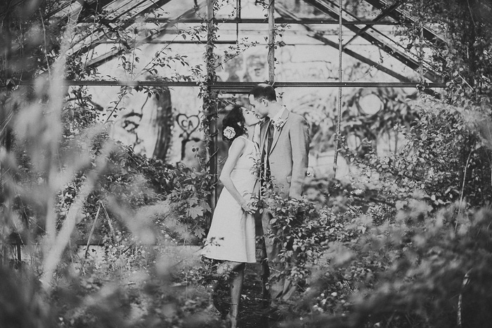 bride and groom kissing in abandoned greenhouse