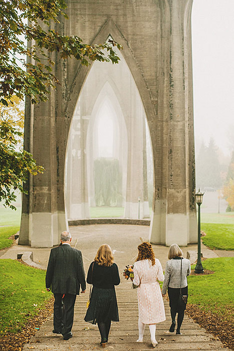 bride walking to ceremony in Cathedral park