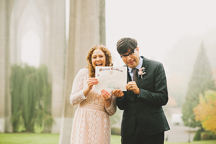 bride and groom holding up marriage certificate