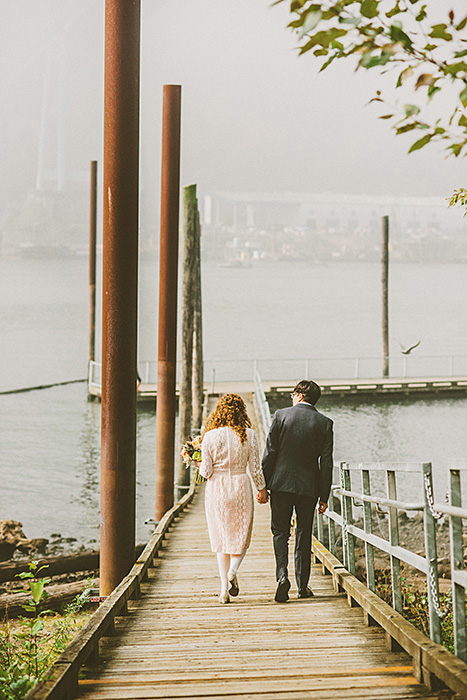 bride and groom walking down the pier