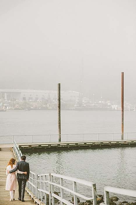 bride and groom walking down pier