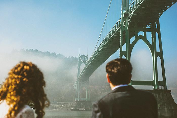 bride and groom looking up at bridge