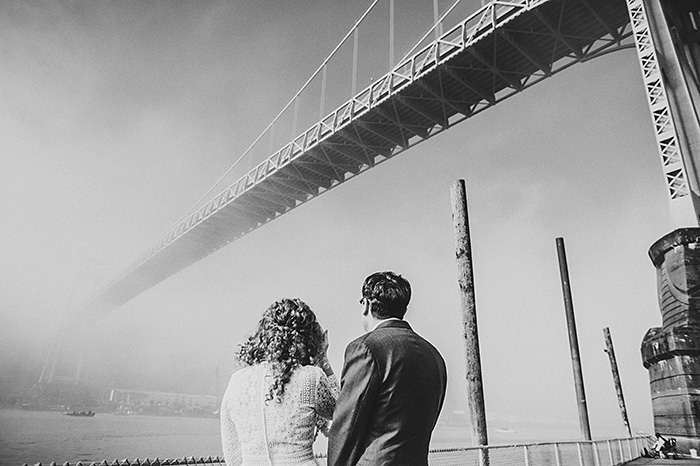bride and groom looking up at bridge