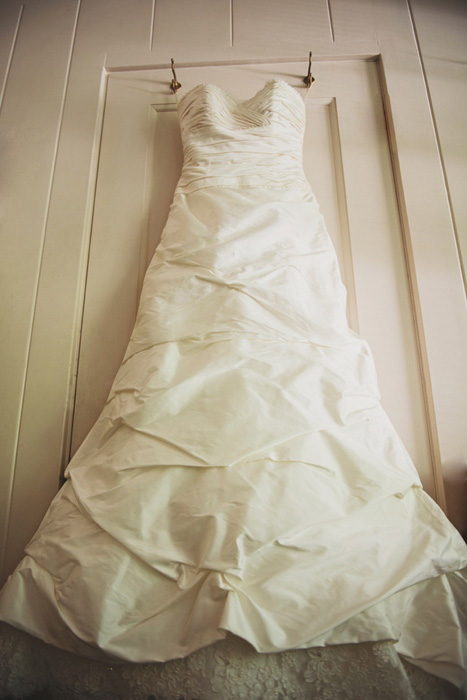 wedding dress hanging in room