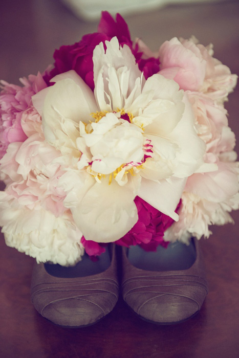 white and pink peony bouquet on wedding shoes