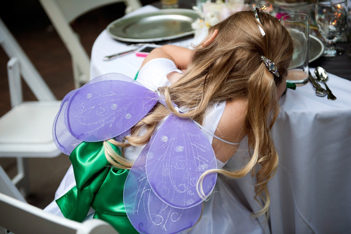 flower girl with wings asleep at table