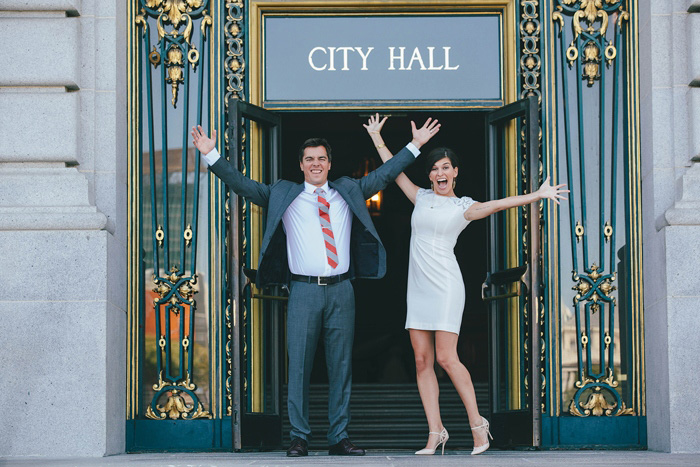bride and groom jumping for joy outside of city hall