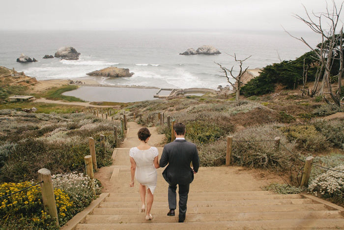 bride and groom walking down stairs to the ocean