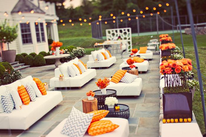 Thiết kế phòng khách với những bộ sofa trắng cùng những chiếc gối ôm màu cam nổi bật.
