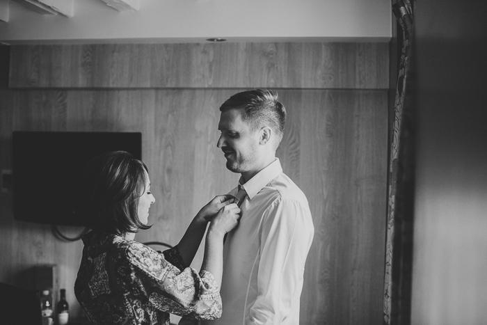 bride helping groom with his tie