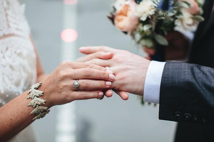 bride placing ring on groom's finger