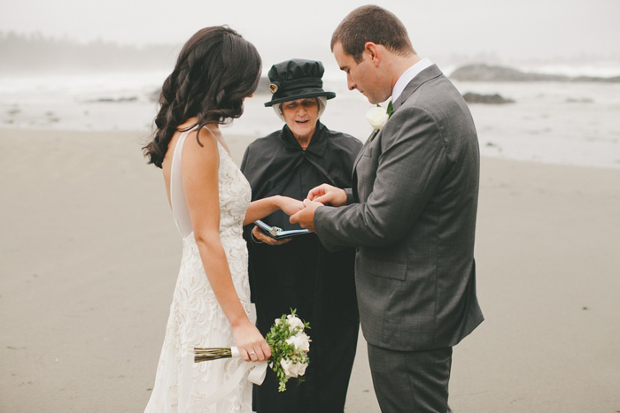 bride and groom exchanging rings on the beach